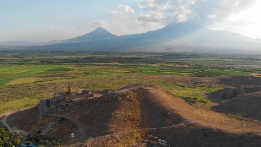 Khor Virap with Mount Ararat in background. The Khor Virap is an Armenian monastery located in the Ararat plain in Armenia, near the border with Turkey. Aerial flight video