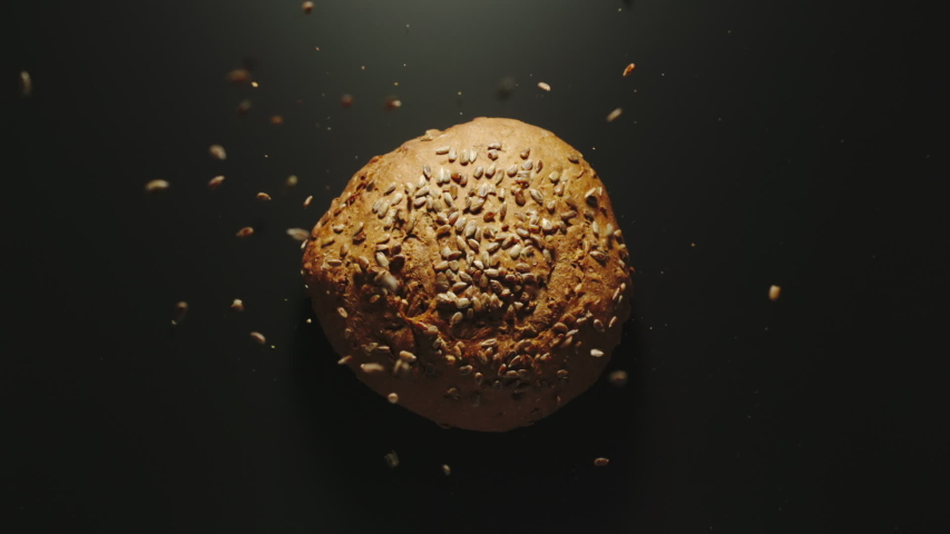 SLOW MOTION: Round Loaf Of Bread With Seeds Falling Down On A Black Surface | Shutterstock HD Video #1035955991