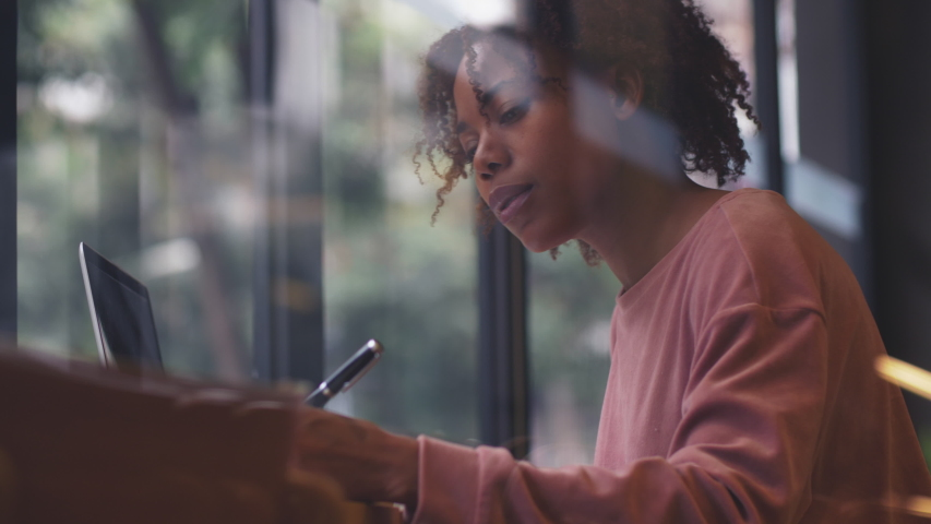 Through the window side view of young black woman female writer writing tinking indoor at cafe thoughtful African freelancer working writing with pen | Shutterstock HD Video #1035957728