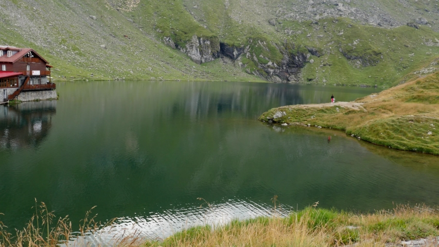 Crystal clear Bale lake with cabin and mountains 4K video | Shutterstock HD Video #1035977531