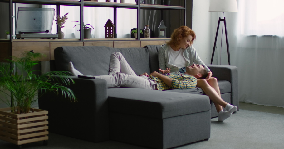 Young couple in love is spending time on sofa at home, laughing, talking, looking at each other, woman is sitting, man is lying near woman, enjoying their relationships. Caucasian. 4K, RED camera. | Shutterstock HD Video #1035987737
