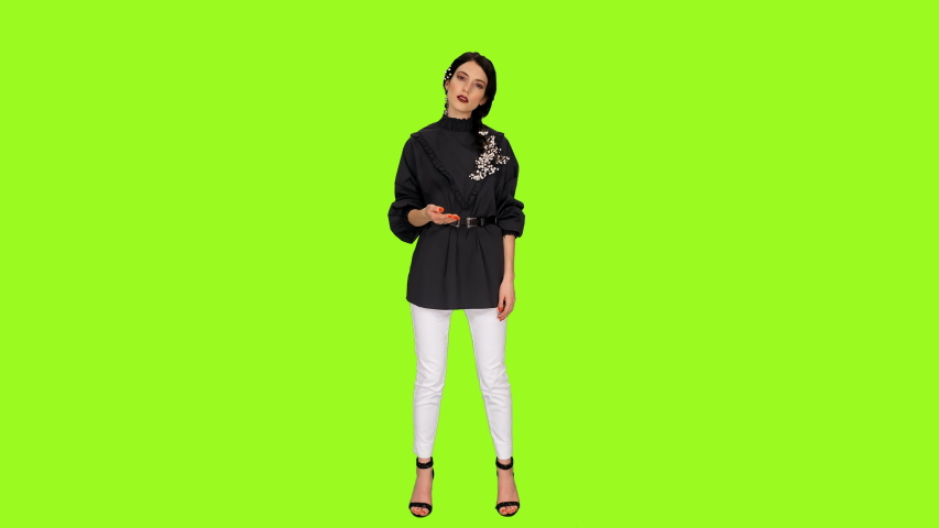 Young stylish brunette woman singing against green screen background, Front view, Chroma key 4k footage