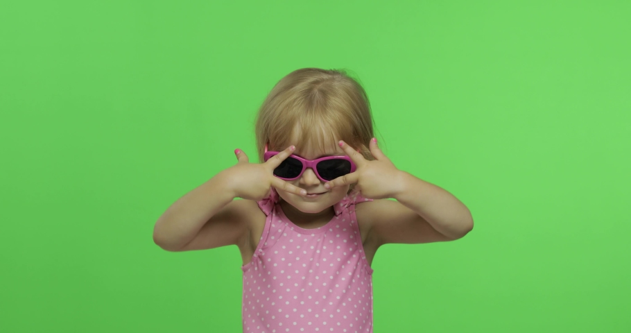 Child in pink swimsuit and sunglasses doing funny sports exercises, girl fitness training and dancing. Happy, pretty little blonde child, 3-4 years old. Make faces and smile. Green screen. Chroma Key