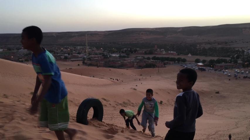 Taghit, Bechar, Algeria - November 03, 2017: Tuareg children are playing on dunes of Sahara Desert.