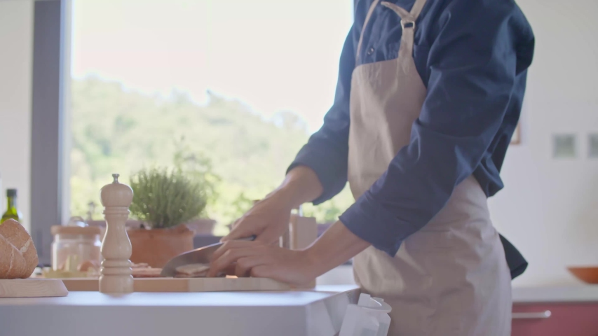 detail of man hand cutting jowl bacon with knife.Young people couple cooking and preparing food,spaghetti pasta carbonara meal for lunch or dinner at modern home open space kitchen.