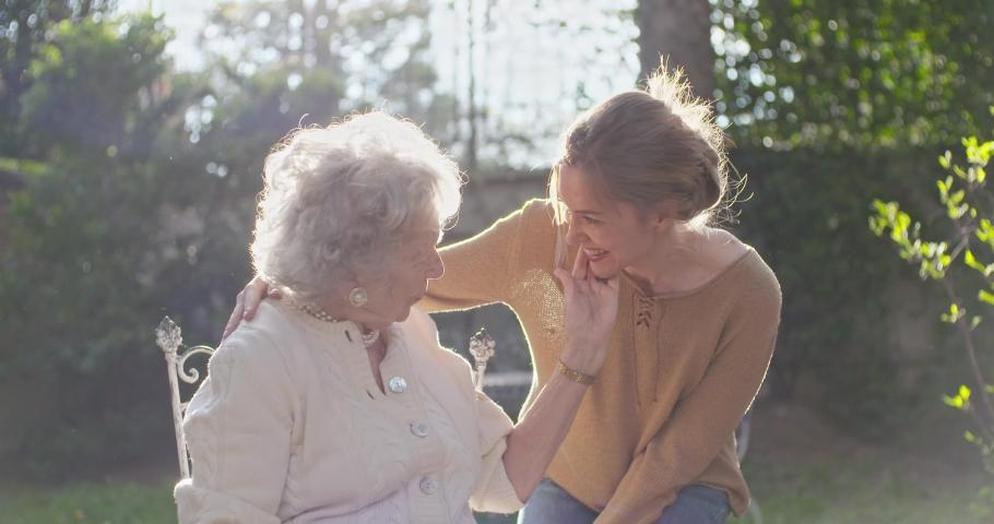Granddaughter visiting,happy hugging grandmother at outside garden,backlight sun. Multigeneration women love holding together.White hair elderly grandma woman.Affection,togetherness,caring,loving