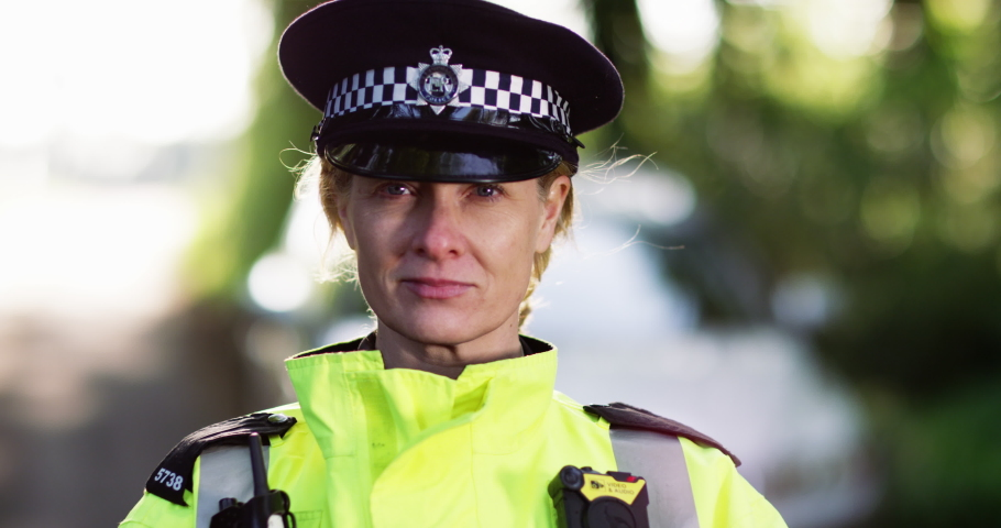 4K Close up portrait of serious female metropolitan police officer out on patrol. Slow motion. | Shutterstock HD Video #1036025342