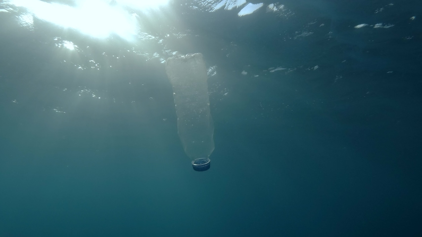 Plastic pollution, plastic bottle in blue water. Discarded plastic bottle slowly drifting under surface of blue water in sunlight. Plastic garbage environmental pollution problem in Mediterranean Sea