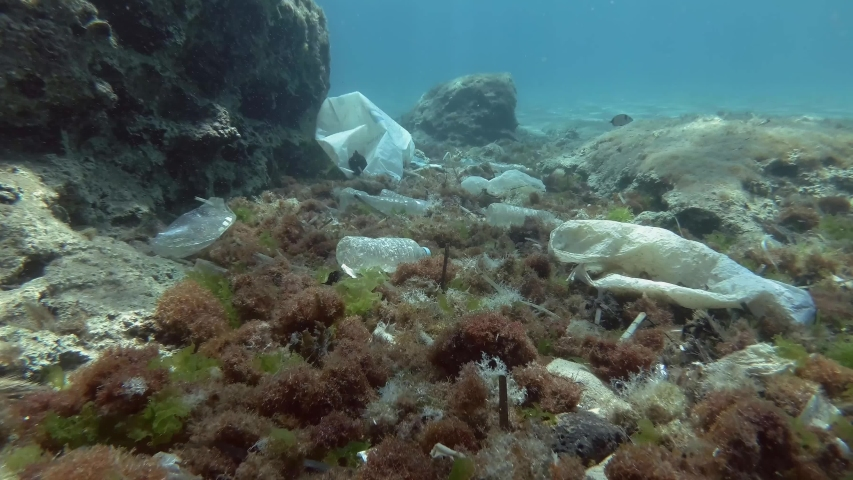 Slow motion. Plastic pollution of the ocean bottom, Tropical fishes swims over the bottom covered with a lot of plastic garbage. Bottles, bags and other plastic debris on seabed in Mediterranean Sea