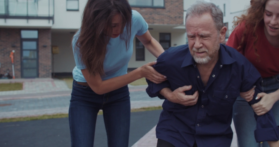 Portrait of stressed adult man feeling sharp chest pain as risk of heart attack in the street. In background two helpful girls running raising him up leading to the hospital.