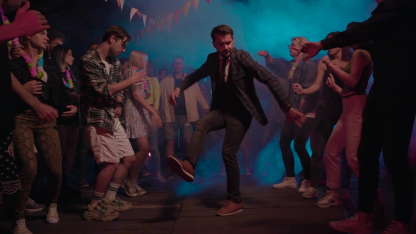 Modern businessman performing cool urban dance in front of delighted nice mood boys and girls dancing in neon lights in nightclub for entertainment.