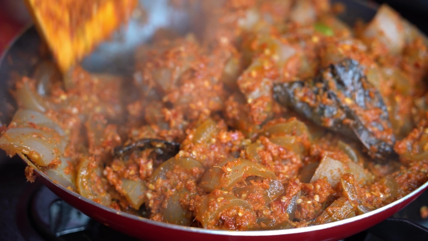 Frying pan with onion, beef stomach, red pepper and sauce, close up. Indonesia. Indonesian cuisine, spicy beef stomach meet and sauce garnish with lemongrass leaf and red chili. Cooking food