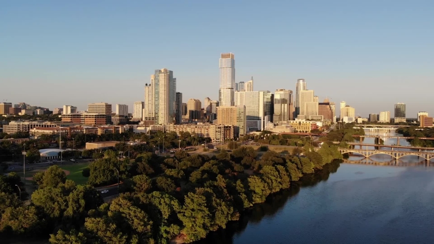 Aerial Drone shot of Downtown Austin, Texas. Shot from the Southwest, coming from Zilker park. Coming over the trees revealing town lake and the downtown skyline.