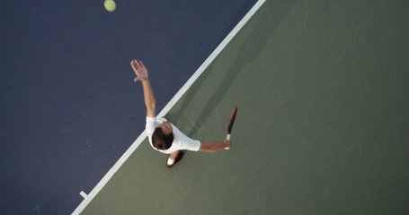 OVERHEAD CRANE Young Caucasian teenager male tennis player serving during a game or practice. Slow motion, 4K UHD RAW graded footage