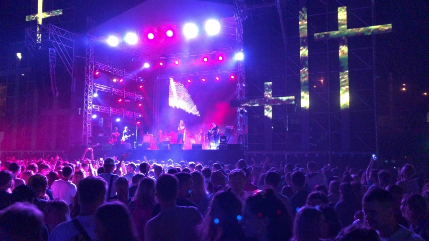 MARIUPOL-9 AUGUST,2019:Group of music fans partying on concert outdoor at night.Summer musical festival City Fest on beach of Azov Sea in Ukraine.Popular entertainment event  #1036081727