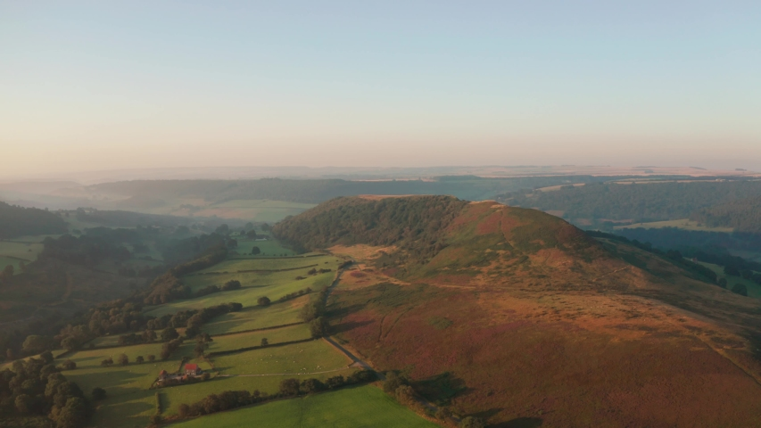 Flying around Hawnby Hill in the North York Moors national park, England UK, during a beautiful sunrise on a hazy summers day, with soft light hitting the heater and surrounding fields. | Shutterstock HD Video #1036083476