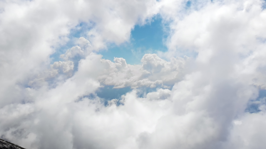 Flying through amazingly beautiful cloudscape. Picturesque timelapse of white fluffy clouds moving softly on the clear blue sky. Direct view from the cockpit. Royalty-Free Stock Footage #1036084160