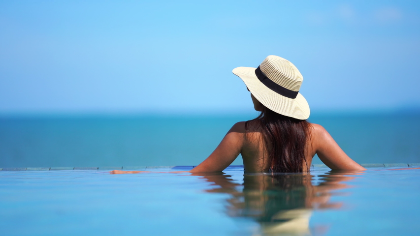 Rear shot of a beautiful lady sitting on the edge of an infinity pool wearing looking at the ocean