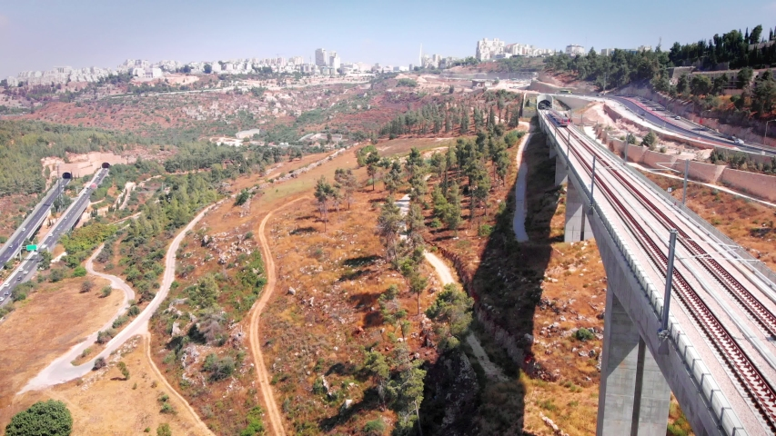 Modern passenger train crossing a bridge in the outskirts of Jerusalem, Aerial footage Drone footage over Jerusalem Entrance bridge with Modern passenger train  | Shutterstock HD Video #1036103300