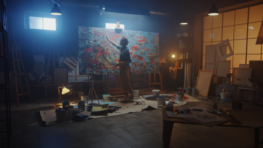 Talented Female Artist Works on Abstract Oil Painting, Using Paint Brush She Creates Modern Masterpiece. Dark and Messy Creative Studio where Large Canvas Stands on Easel Illuminated. Zoom out | Shutterstock HD Video #1036107533