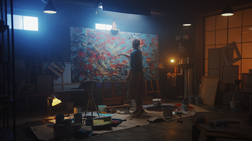 Talented Female Artist Works on Abstract Oil Painting, Using Paint Brush She Creates Modern Masterpiece. Dark and Messy Creative Studio where Large Canvas Stands on Easel Illuminated. Zoom out Royalty-Free Stock Footage #1036107545