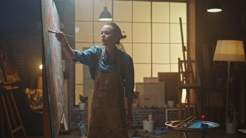Female Artist Works on Abstract Oil Painting, Moving Paint Brush Energetically She Creates Modern Masterpiece. Dark Creative Studio where Large Canvas Stands on Easel Illuminated. Zoom in Shot