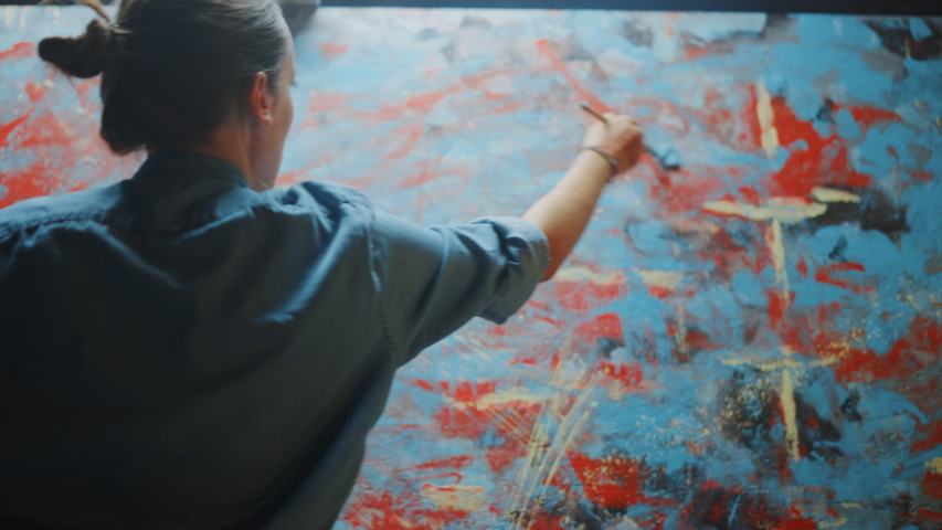 Talented Innovative Female Artist Picks up Paint Brush and Starts Drawing Colorful, Emotional, Sensual Oil Painting. Contemporary Painter Creating Abstract Modern Art in Her Studio