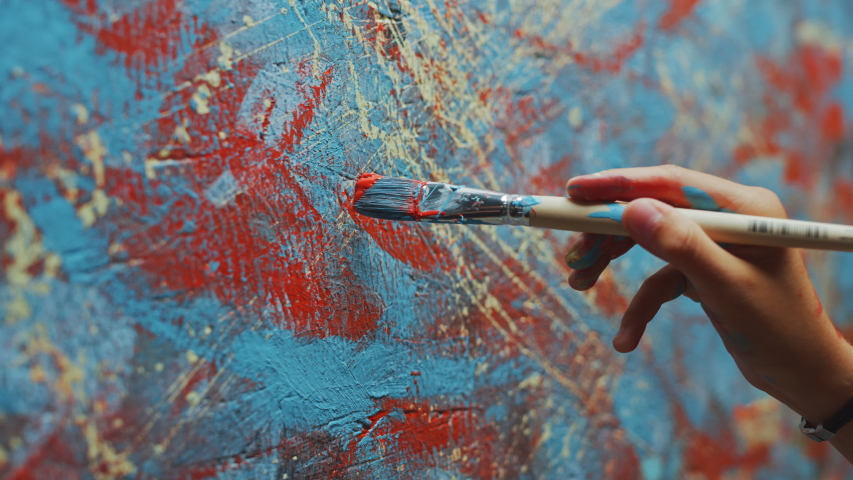 Close-up Shot of Female Artist Hand, Holding Paint Brush and Drawing Oil Painting. Colorful, Emotional Oil Painting. Contemporary Painter Creating Modern Abstract Piece of Fine Art