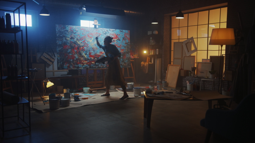 Talented Female Artist Working on a Modern Abstract Oil Painting, Uses Splattering and Dripping with Paint Brush Technique. Dark Creative Studio Large Picture Stands on Easel Illuminated. Slow Motion #1036107914