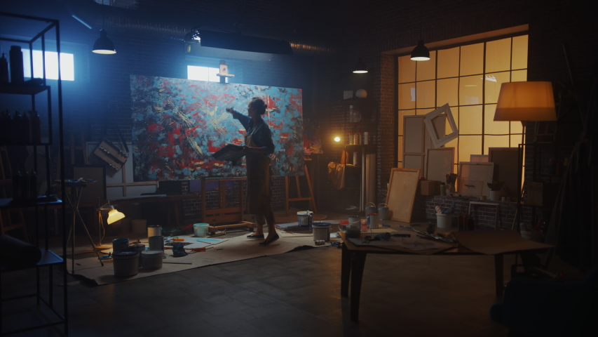 Talented Female Artist Working on a Modern Abstract Oil Painting, Uses Splattering and Dripping with Paint Brush Technique. Dark Creative Studio Large Picture Stands on Easel Illuminated. Slow Motion #1036107917