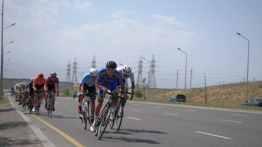 ALMATY / KAZAKHSTAN - AUGUST 30, 2019: Cycle race Tour of Almaty 2019. Peloton athletes moves on the highway on the outskirts of the city. Slow motion