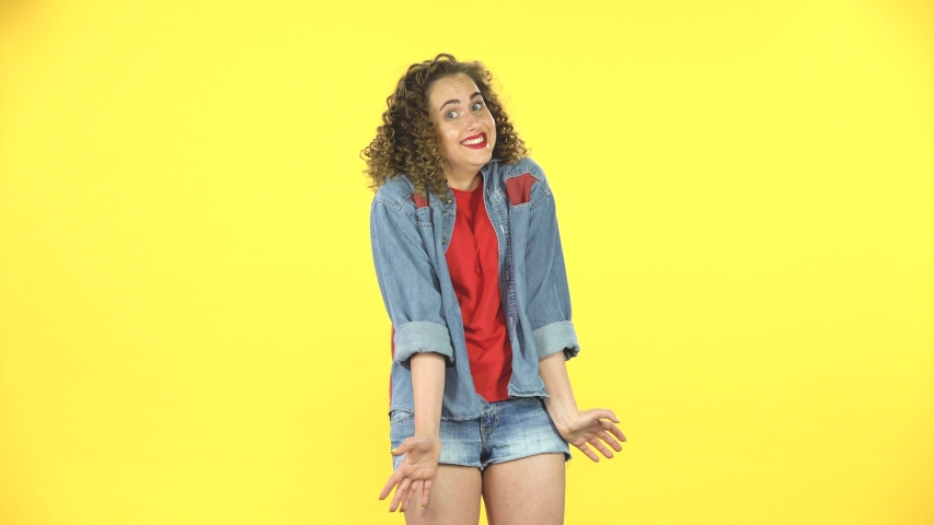 Curly woman throwing up hands expressing she is innocent, saying oops she doesn't know what's going. Yellow background at studio. Girl with curly hair in a denim suit with shorts and a red T-shirt. | Shutterstock HD Video #1036113677