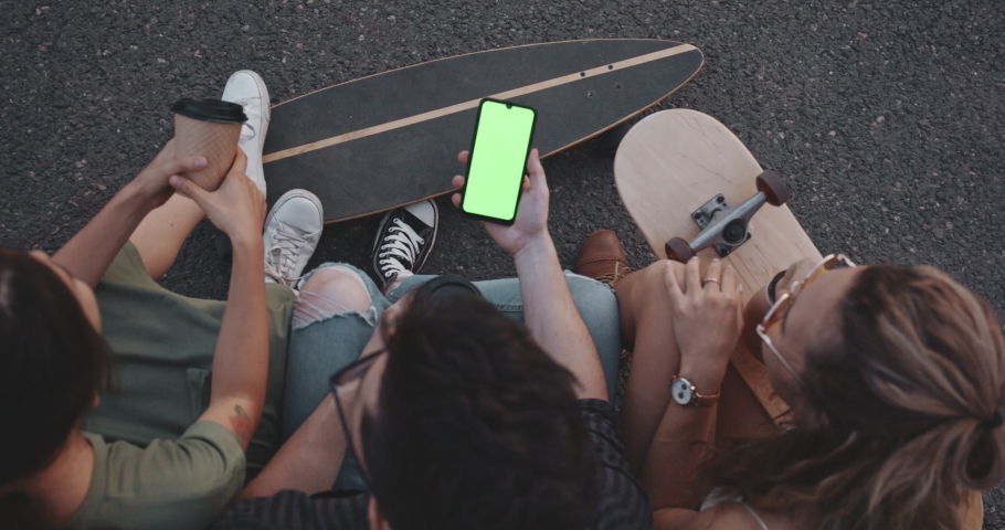 Young millennial friends sitting outside with coffee and looking at green screen phone in park. Happy smiling people using modern smartphone technology. Media, lifestyle, internet education concept | Shutterstock HD Video #1036121225