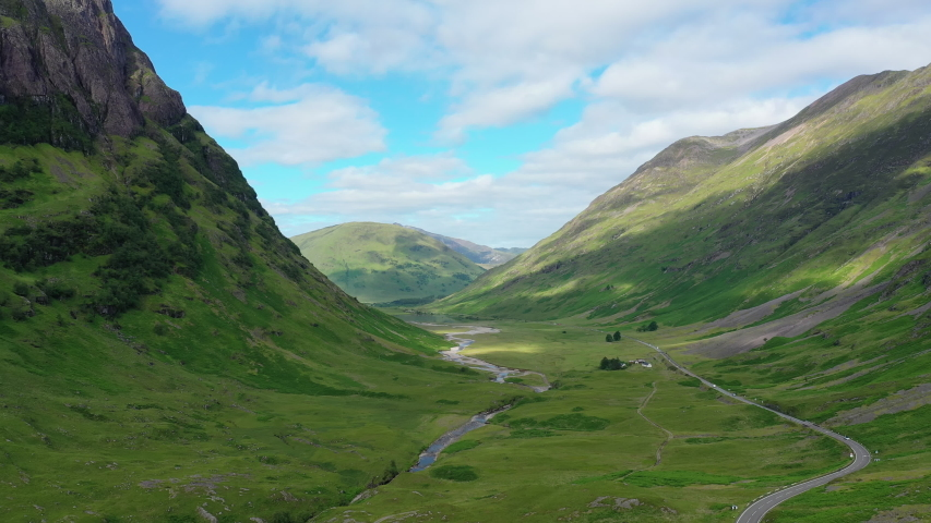 Aerial view of picturesque landscape of Glen Coe, scenic valley in Highlands of Scotland, lush green hills - panorama of Scotland from above, United Kingdom, Great Britain, Europe