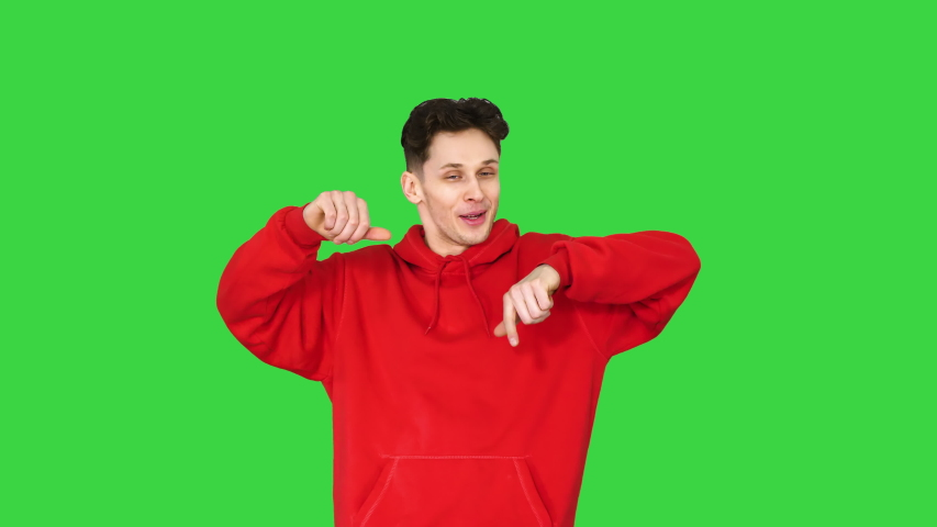 Young caucasian man dancer in red hoody talking to camera on a Green Screen, Chroma Key.
