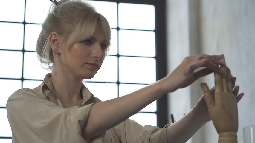 Female artist woman (designer) working with wooden hand. Slowmotion. #1036131782