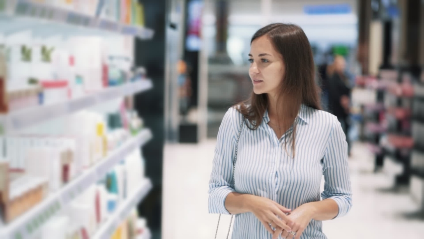 Beautiful young woman goes among shelves and looks at goods in cosmetics shop, slow motion. Steadicam shot. Concept of purchases, mall | Shutterstock HD Video #1036133954