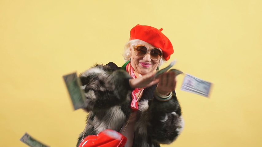 Rich elegant woman in fur coat and red cap throwing money, spending money on useless thing, isolated yellow background. studio shot | Shutterstock HD Video #1036143755