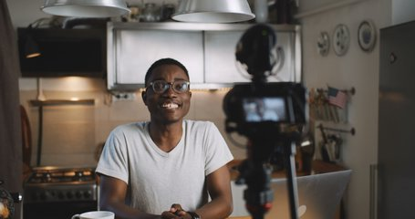 Happy young smart black blogger man filming new vlog video with professional camera in kitchen at home slow motion.