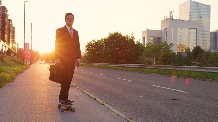 SLOW MOTION, LENS FLARE: Cool sporty businessman going home from work on his e-skateboard. Cheerful yuppie cruising through the city on a sunny summer evening. Happy young man enjoying his ride home. | Shutterstock HD Video #1036153754