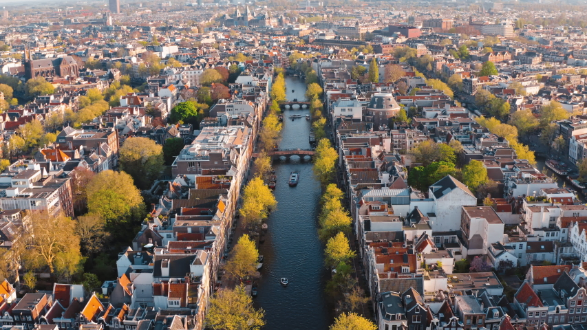 Amsterdam, Netherlands: drone flight along narrow canal with boats in the center city | Shutterstock HD Video #1036155341
