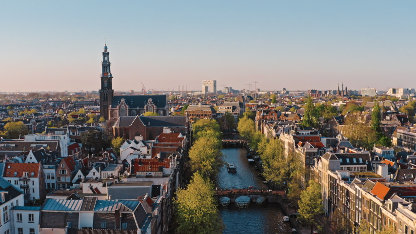 Amsterdam, Netherlands: drone view of Westerkerk church and narrow canal with bridges and boats traffic