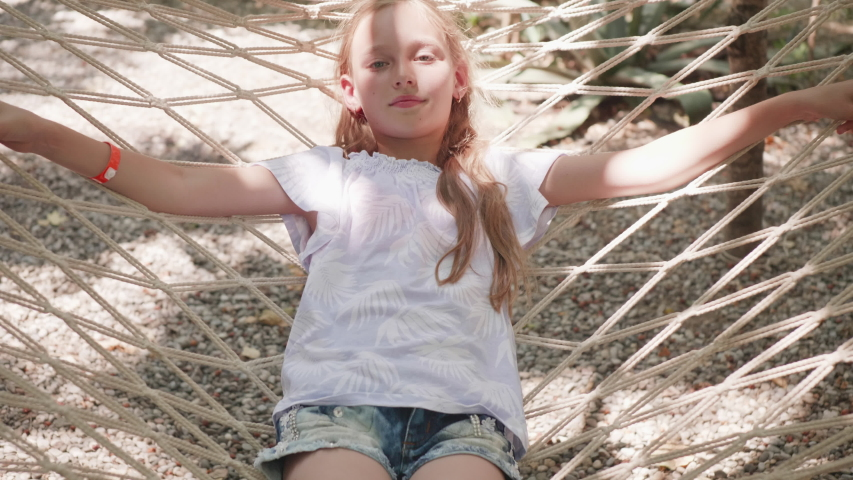 Relaxing girl swinging in hammock at summer day. Happy girl resting in hammock while summer vacation | Shutterstock HD Video #1036160027