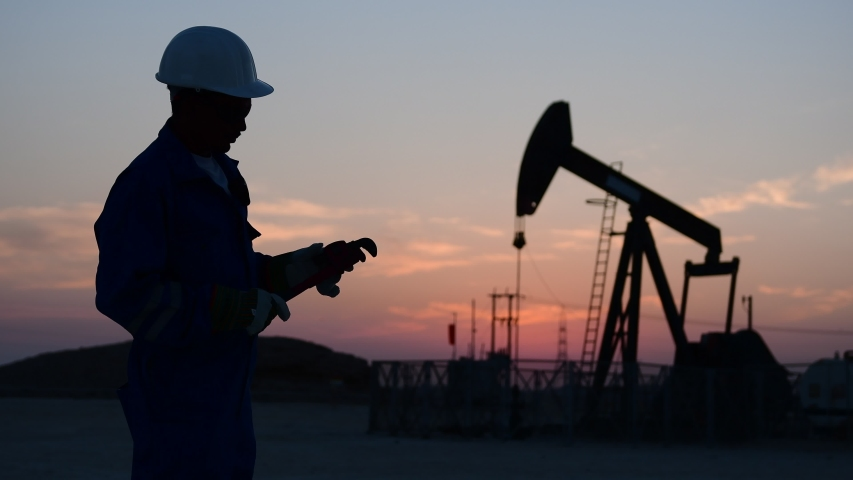 Silhouette of a technical oilfield worker monitoring crude oil pump at sunset. Royalty-Free Stock Footage #1036162307