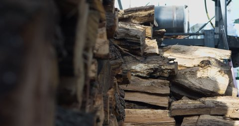A pile of wood for burning in BBQ pits with a smoker behind it. 4k