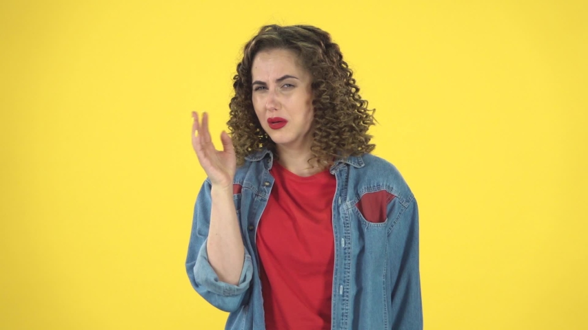 Woman showing disgust for bad smell or taste on yellow background at studio, slow motion. Girl with curly hair in a denim suit with a red T-shirt. Concept of emotions | Shutterstock HD Video #1036171790