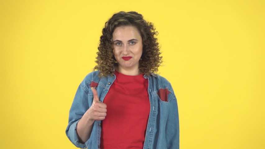 Cheerful girl carefully examines something and nods approvingly, then showing thumbs up, gesture like, over yellow background at studio, slow motion. Girl in a denim suit with shorts and a red T-shirt | Shutterstock HD Video #1036171820
