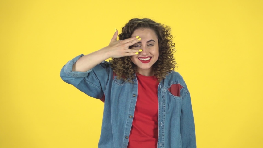 Girl making funny faces with her fingers looking at the camera on yellow background at studio, slow motion. Girl in a denim suit with shorts and a red T-shirt | Shutterstock HD Video #1036171847