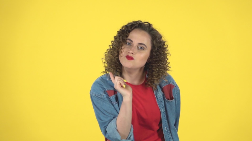 Girl listens carefully, angry and waves her head negatively on yellow background at studio, slow motion. Girl with curly hair in a denim suit with shorts and a red T-shirt | Shutterstock HD Video #1036171928
