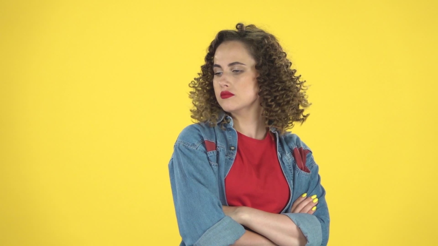 Funny female smiles and rejoices then offended on yellow background at studio, slow motion. Girl with curly hair in a denim suit with a red T-shirt | Shutterstock HD Video #1036171946